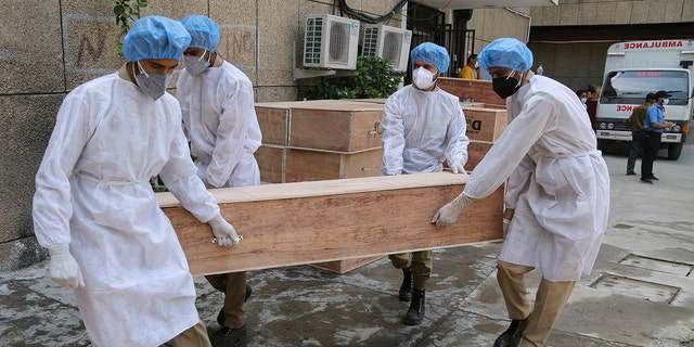 May 19, 2021: Jammu and Kashmir State Disaster Response Force soldiers carry empty coffins for transporting bodies of people who died of COVID-19 outside government medical hospital in Jammu, India.