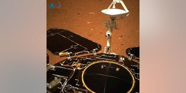Dalam gambar yang diambil oleh penjelajah Mars Zhurong Tiongkok dan disediakan oleh Administrasi Luar Angkasa Nasional Tiongkok (CNSA) pada hari Rabu, 19 Mei 2021, panel surya dan antena penjelajah dikerahkan saat penjelajah sedang duduk di pendarat Mars.  China mendaratkan pesawat ruang angkasa di Mars untuk pertama kalinya pada hari Sabtu, prestasi teknis yang lebih sulit daripada pendaratan di bulan, dalam langkah maju terbaru untuk mencapai tujuan ambisiusnya di luar angkasa.  (CNSA melalui AP)