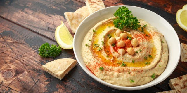 Hummus is made from cooked and mashed chickpeas. The dish is often mixed with olive oil, lemon, garlic and other seasonings. Many people serve hummus with chips, bread or vegetables. (iStock)