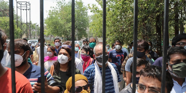 May 10, 2021: In this file photo, people waiting to get vaccinated against the coronavirus stand outside the closed gates of a hospital in Ghaziabad, outskirts of New Delhi, India.