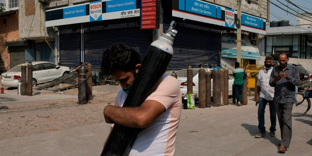 May 3, 2021: A man walks carrying a refilled cylinder as family members of COVID-19 patients wait in line to refill their oxygen cylinders at Mayapuri area in New Delhi, India.