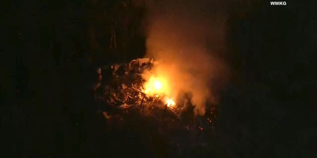 Fire can be seen in the area where a helicopter crashed near an airport in Leesburg, Florida on Tuesday.