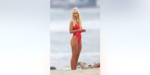 """Lily James in costume as Pamela Anderson in her iconic red """"Baywatch"""" swimsuit."""