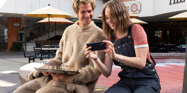 """This image released by IFC Films shows Andrew Garfield, left, and Maya Hawke in a scene from """"Mainstream,"""" a film by Gia Coppola."""
