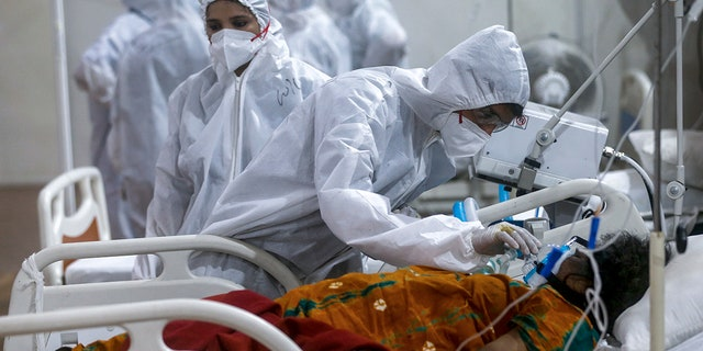 May 6, 2021: A health worker tries to adjust the oxygen mask of a patient at the BKC jumbo field hospital, one of the largest COVID-19 facilities in Mumbai, India.