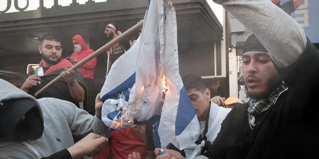 Pro-Palestinian protesters burn the Israeli flag in New York City on Thursday. (Getty Images)