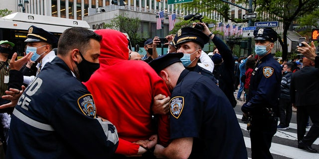 NYPD officers detain a pro-Palestinian supporter near the Israeli Consulate on Tuesday. (Reuters)
