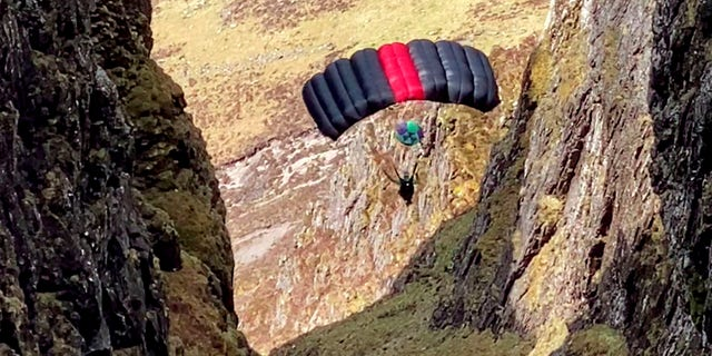 Nick Cowie filmed a base jumper leap off Aonach Eagach inGlen Coe, Scotland, and parachute through the narrow ridge.