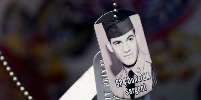 A relative of SP4 Donald Sargent wears his dog tags at the unveiling of a monument to honor the military passengers of Flying Tiger Line Flight 739, Saturday, May 15, 2021, in Columbia Falls, Maine. Sargent was among those killed on the secret mission to Vietnam in 1962. (Associated Press)