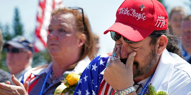 John Biernacki of Greenville, Texas, wipes tears during the unveiling of a monument to honor the military passengers of Flying Tiger Line Flight 739, Saturday, May 15, 2021, in Columbia Falls, Maine. His father, MSgt., Henry Biernacki, was among those killed on the secret mission to Vietnam in 1962. (Associated Press)