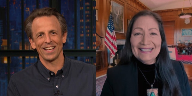 Comedian Seth Meyers called out a Deb Haaland staffer when he caught the cameraman crawling on the floor in the background during a Tuesday interview on 'Late Night with Seth Meyers.'