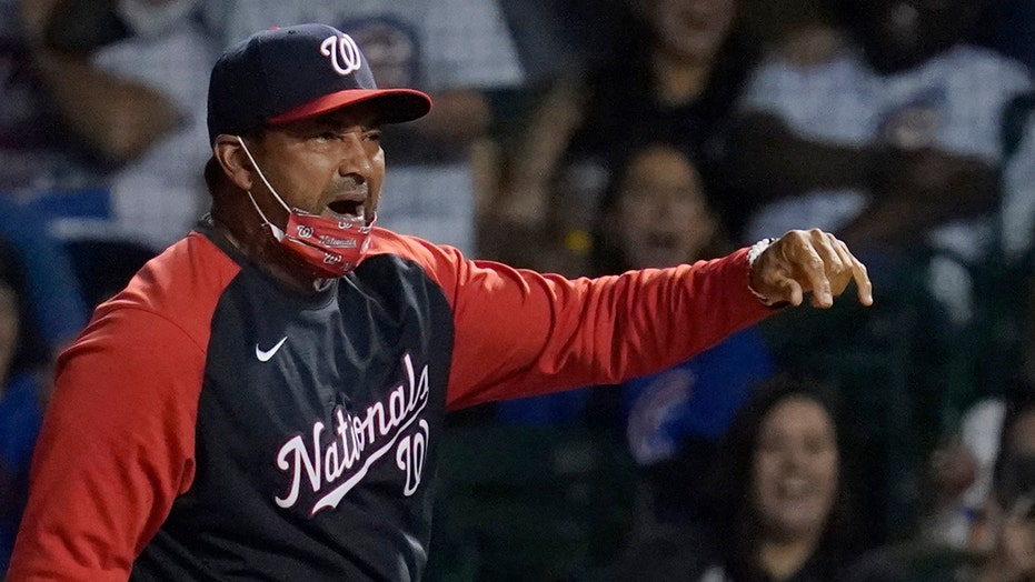 Nationals' Dave Martinez throws first base after getting ejected from game