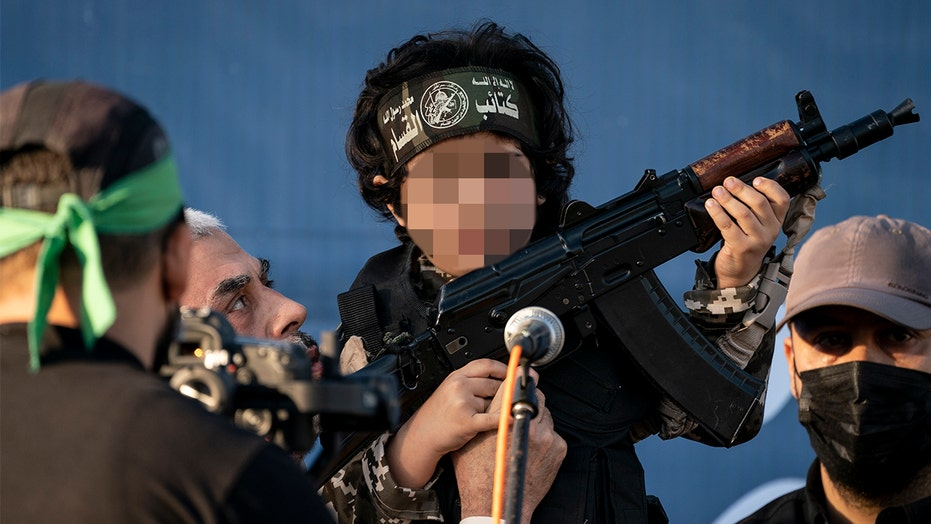 Hamas leader Sinwar hoists rifle-carrying child for cameras in Gaza City rally