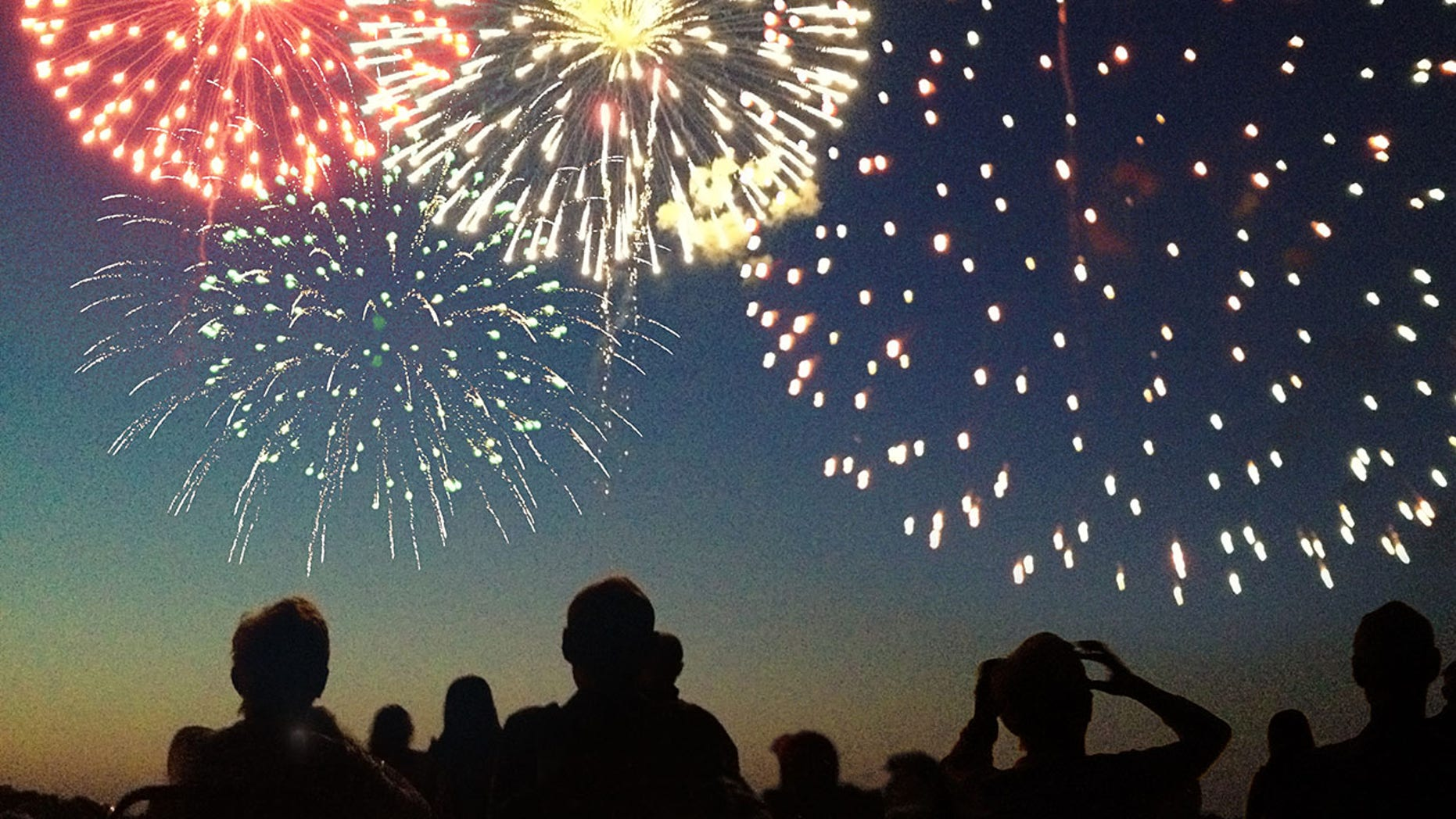 Fourth of July Fireworks Exploding Over Celebrating Spectators in Silhouette