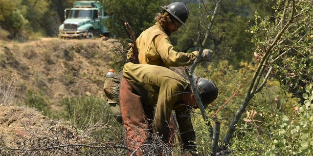 A group of firefighting monks was ready to defend a Buddhist monastery being threatened Tuesday by a wildfire burning in the rugged central coast mountains south of Big Sur.