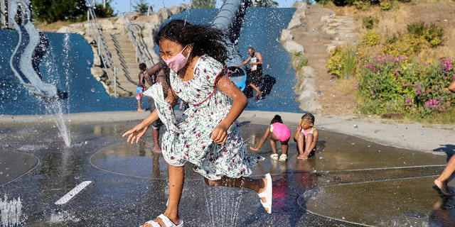 Isis Macadaeg, edad 7, plays in a spray park at Jefferson Park during a heat wave in Seattle, Washington, U.S., en Junio 27, 2021. REUTERS/Karen Ducey