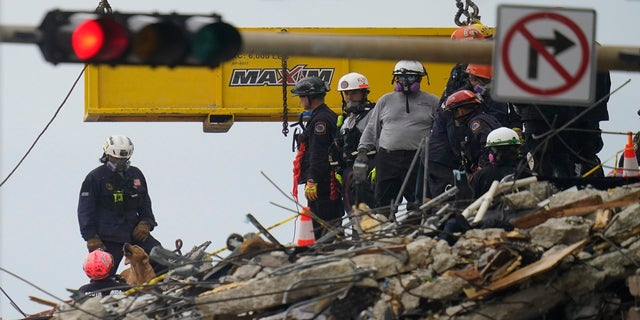A dog working with search and rescue personnel barks to alert them after sniffing a spot atop the rubble at the Champlain Towers South condo building on Wednesday. (AP)