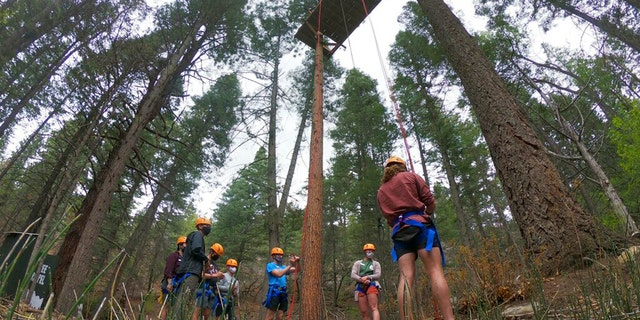 Before the campers arrive in June, the Glorieta Adventure Camp instructors practice abseiling in the trees.  Campers and staff will be kept in groups of 10 or less, wear masks outside their dormitories, and eat outside to avoid outbreaks.  (AP Photo / Cedar Attanasio)