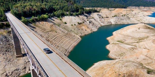 یک اتومبیل روز یکشنبه ، 23 مه 2021 ، در اوروویل ، کالیفرنیا از پل Enterprise بر روی سواحل خشک دریاچه Oroville عبور می کند.  در زمان تهیه این عکس ، مخزن 39 درصد ظرفیت و 46 درصد میانگین تاریخی آن بود.  (آسوشیتدپرس)