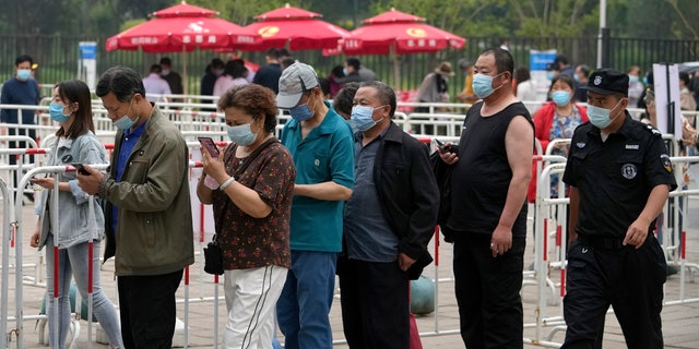 June 2, 2021: A security guard watches residents wearing face masks to help curb the spread of the coronavirus line up to receive the Sinopharm COVID-19 vaccine at a vaccination center in the Central Business District in Beijing.