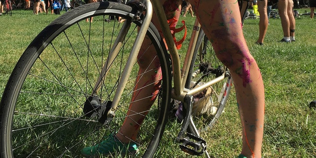 Olivia Neely, a topless cyclist wearing body paint, motions before the start of that year's annual Philly Naked Bike Ride in Philadelphia on Sept. 9, 2017. (AP Photo/Dino Hazell, lêer)