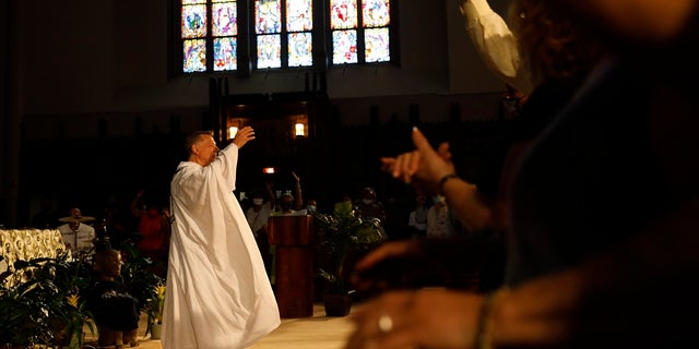 Parishioners raise their hands as Rev. Michael Pfleger conducts his first Sunday church service as a senior pastor at St. Sabina Catholic Church following his reinstatement by Archdiocese of Chicago after decades-old sexual abuse allegations against minors, Domenica, giugno 6, 2021, in the Auburn Gresham neighborhood in Chicago. (AP Photo/Shafkat Anowar)
