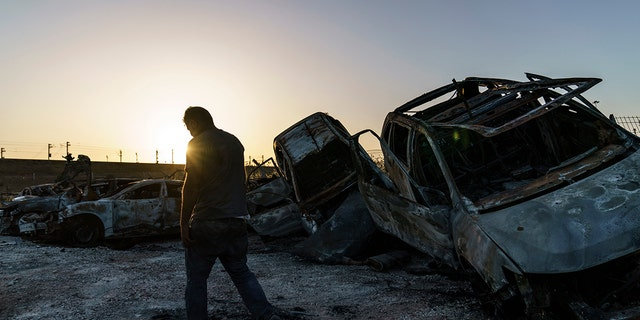 A worker passes torched cars piled up in a lot from clashes between Arabs, polisie, and Jews in the mixed Arab-Jewish town of Lod, central Israel, Dinsdag, Mei 25, 2021.  (AP Photo/David Goldman)