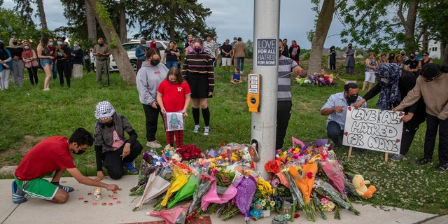 People attend a memorial at the site where a family of five was hit by a driver in London, Ontario, on Monday, June 7, 2021.