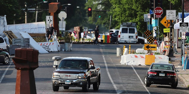 The vehicle travels on Chicago Ave.  S. Near E. 38th St.  at George Floyd Square, Tuesday, June 8, 2021, in Minneapolis, after city crews returned to GFS to remove debris and barriers for the second time in an attempt to open the intersection to traffic.  (David Jolles / Star Tribune via AP)