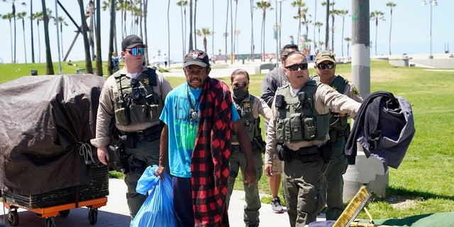Members of the Los Angeles County Sheriff's Department's HOST, Homeless Outreach Service Team, walk with a homeless man on Tuesday in the Venice Beach section of Los Angeles. (AP Photo/Marcio Jose Sanchez)