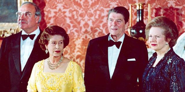 La fotografía de archivo del 10 de junio de 1984 muestra a la reina Isabel II, segunda a la izquierda, de pie con el canciller de Alemania Occidental Helmut Kohl, a la izquierda, el presidente de los Estados Unidos, Ronald Reagan, segunda a la derecha, y la primera ministra británica Margaret Thatcher en el Palacio de Buckingham de Londres, antes de una cena para líderes de la cumbre.  (Foto AP, Archivo)