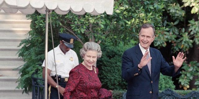 En esta fotografía de archivo del 15 de mayo de 1991, el presidente de los Estados Unidos, George HW Bush, escolta a la reina Isabel II desde la Casa Blanca hasta un helicóptero en ruta a Baltimore para ver su primer partido de béisbol en las Grandes Ligas, en Washington.  (Foto AP / Doug Mills, archivo)
