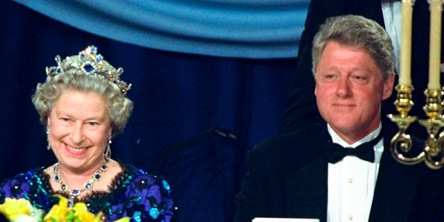 En esta fotografía de archivo del sábado 4 de junio de 1994, la reina Isabel de Gran Bretaña sonríe mientras se sienta junto al presidente Bill Clinton en una cena en el Guildhall de Portsmouth, Inglaterra, para conmemorar el 50 aniversario del Día D.  (Foto AP / Doug Mills, archivo)