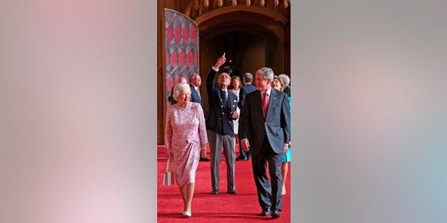En esta fotografía de archivo del 15 de junio de 2008, la reina Isabel II y el príncipe Felipe, duque de Edimburgo, señalando, caminan con el presidente estadounidense George Bush y su esposa Laura, en St George's Hall, el castillo de Windsor, en Windsor, Inglaterra.  (Nick Ray, Foto de la piscina a través de AP, archivo)