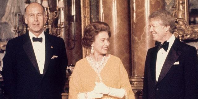 En esta foto de archivo de mayo de 1977, el presidente estadounidense Jimmy Carter, a la derecha, y la reina Isabel II junto al presidente francés Valery Giscard d'Estaing en el Palacio de Buckingham en Londres.  (Foto AP, Archivo)