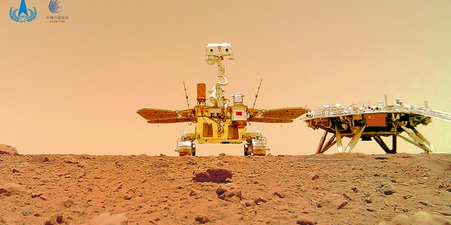 In this image, released by the China National Space Administration (CNSA) on Friday, June 11, 2021, the Chinese Mars Rover Zhurong is seen near its landing platform taken by a remote camera dropped in position by the rover.  China on Friday released a series of photos taken of its Zhurong rover on the surface of Mars, including one of the rover itself taken by a remote camera.  (CNSA via AP)