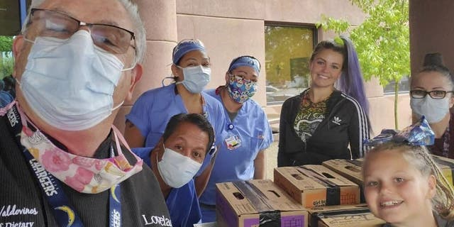 Henrique Valdovinos (left), and other health care workers at the Lovelace Women's Hospital in Albuquerque, New Mexico, received a cookie donation from the Girl Scouts of New Mexico Trails. The donation was a part of the troop's Hometown Heroes program. (Girl Scouts of New Mexico Trails via AP)