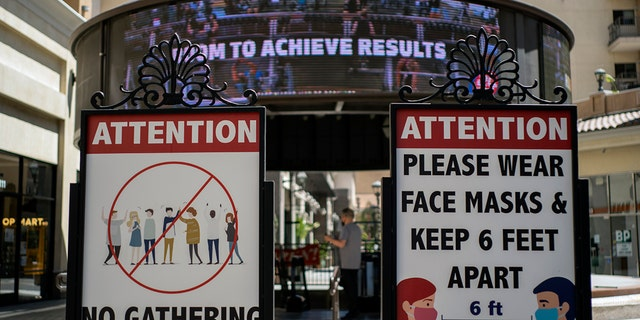 Signs with social distancing guidelines and face mask requirements are posted at an outdoor mall amid the coronavirus pandemic in Los Angeles on Friday, June 11, 2021. (Associated Press)