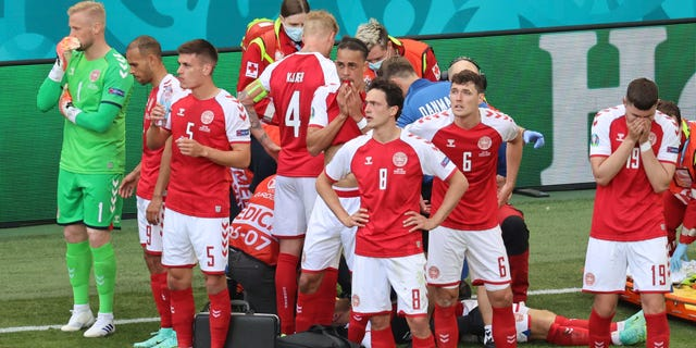Denmark's players react as their teammate Christian Eriksen lies on the ground during the 2020 European Football Championship match between Denmark and Finland at the Parken Stadium in Copenhagen, Denmark, Saturday, June 12, 2021.  (Wolfgang Rattay / Pool via AP)