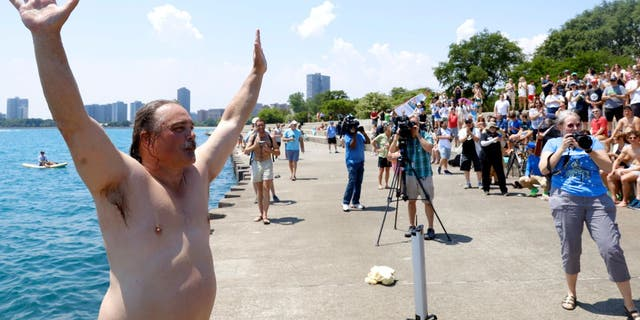 """Dan O'Conor, the """"Great Lake Jumper,"""" reacts after making his 365th leap into Lake Michigan, Saturday, June 12, 2021, in Chicago's Montrose Point."""