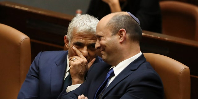 Israel's new prime minister, Naftali Bennett, sits with Yair Lapid, left, during a Knesset session in Jerusalem Sunday, June 13, 2021. Israel's parliament has voted in favor of a new coalition government, formally ending Prime Minister Benjamin Netanyahu's historic 12-year rule. (AP Photo/Ariel Schalit)