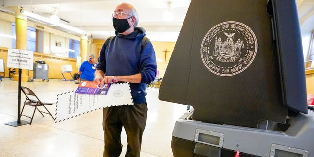 Rafael Risember, 62, prepares to scan his ballot as he participates in early voting in the primary election, Monday, June 14, 2021, at the Church of St. Anthony of Padua in the Soho neighborhood of New York. (AP Photo/Mary Altaffer)