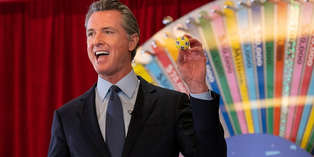 FILE - In this June 4, 2021, file photo, California Gov. Gavin Newsom holds up a lottery ball at the California Lottery Headquarters on Friday, June 4, 2021, in Sacramento, Calif., while drawing numbers for California's new vaccine incentive program. California, the first state in America to put in place a coronavirus lockdown, is now turning a page on the pandemic. Most of California's coronavirus restrictions will disappear Tuesday, June 15, 2021. (Paul Kitagaki Jr./The Sacramento Bee via AP, File)/The Sacramento Bee via AP)