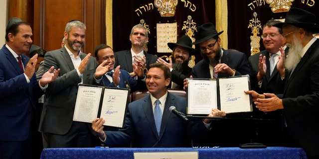 Surrounded by state legislators and Jewish leaders, Florida Gov. Ron DeSantis, center, holds up two bills that he signed, Monday, June 14, 2021. (AP Photo/Wilfredo Lee)