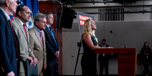 Rep. Marjorie Taylor Greene, R-Ga., right, accompanied by from left, Rep. Mo Brooks, R-Ala., Rep. Bob Good, R-Va., Rep. Buddy Carter, R-Ga., and Rep. Thomas Massie, R-Ky., takes a question during a news conference. (AP Photo/Andrew Harnik)
