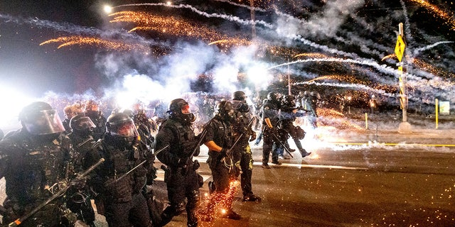 In this Sept. 5, 2020, file photo, police use chemical irritants and crowd control munitions to disperse protesters during a demonstration in Portland, Ore. (AP Photo/Noah Berger, File)