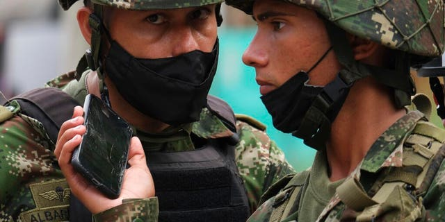Soldiers listen to the news on a mobile phone near the military base where a car bomb exploded in Cucuta, Colombia, Tuesday, June 15, 2021.