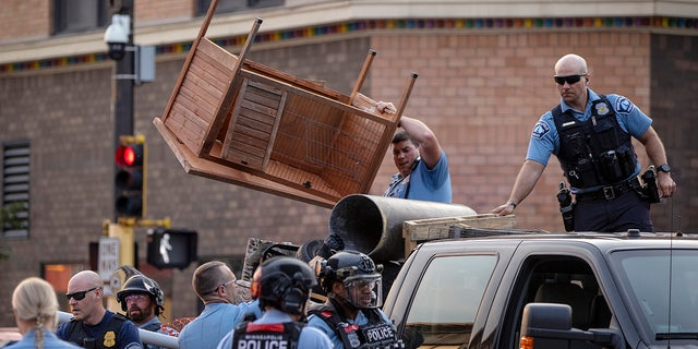 Police clear out items used to barricade Lake Street in the Uptown neighborhood of Minneapolis, Wednesday, June 16, 2021. A St. Paul man accused of speeding up and driving into a group of protesters in Minneapolis while he was drunk, killing one person, was charged Wednesday with intentional second-degree murder. (Carlos Gonzalez/Star Tribune via AP)