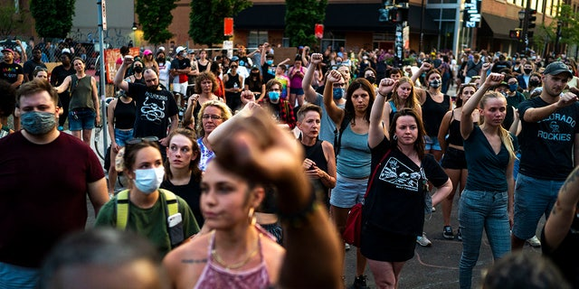 Protesters raise their fists in support during a birthday celebration and protest on West Lake Street in Uptown in honor of Deona Marie Knajdek's birthday on Wednesday, June 16, 2021, in Minneapolis. (Antranik Tavitian/Star Tribune via AP)