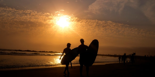 Surfers are silhouetted as they leave the water during the sun set on Wednesday, June 16, 2021, in the Venice Beach section of Los Angeles. An unusually early and long-lasting heat wave brought more triple-digit temperatures Wednesday to a large swath of the U.S. West, raising concerns that such extreme weather could become the new normal amid a decades-long drought.(AP Photo/Ringo H.W. Chiu)